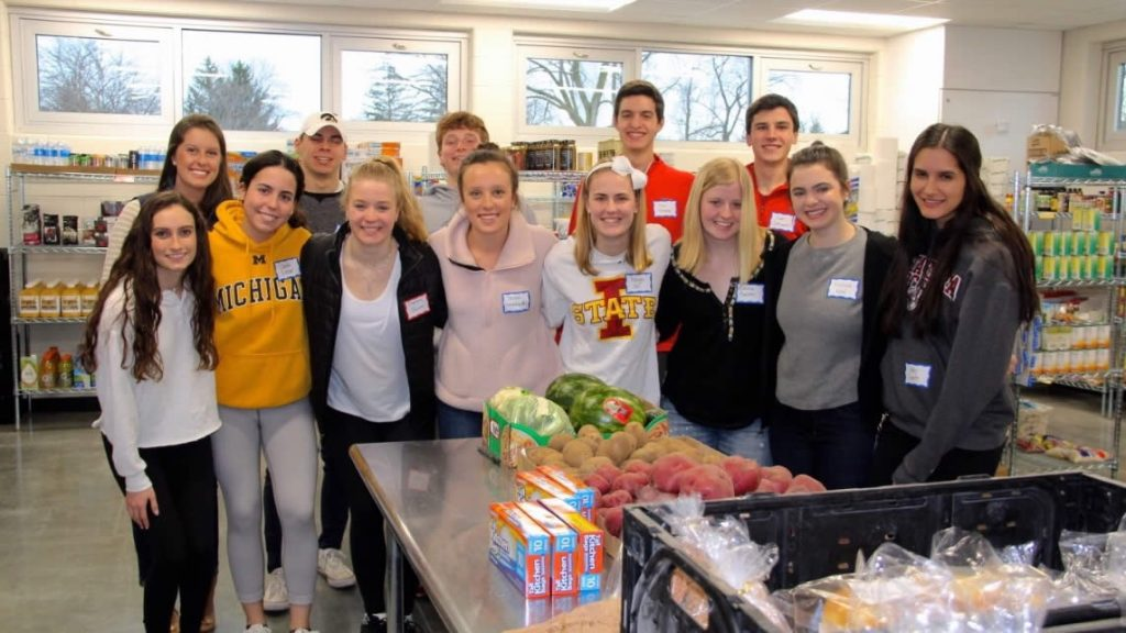 group shot of high school student volunteers wearing college sweatshirts