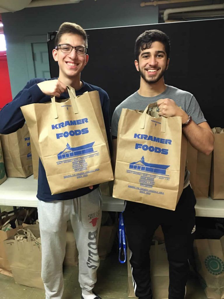 two boys carrying grocery bags
