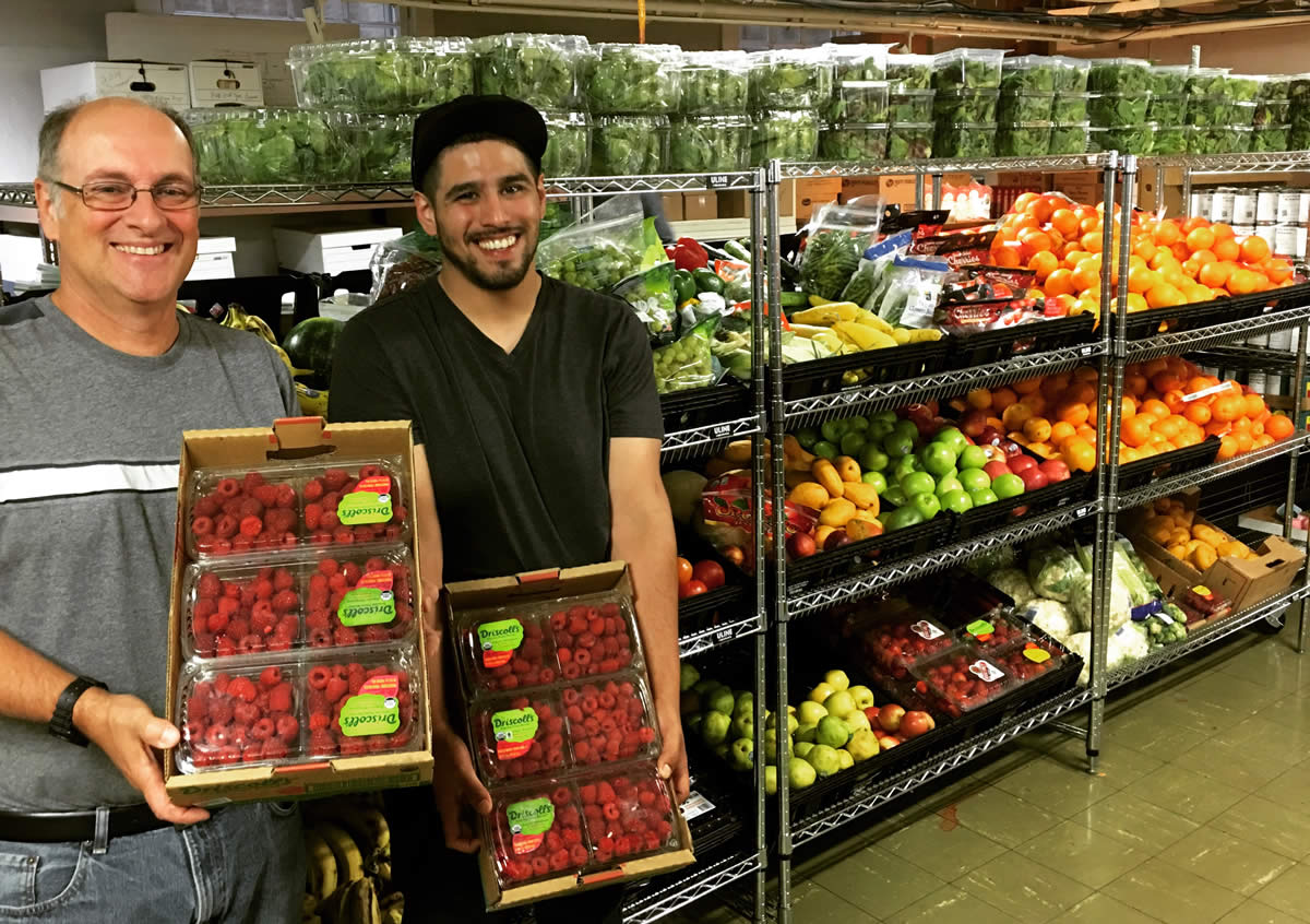 two men holding raspberries in front of produce