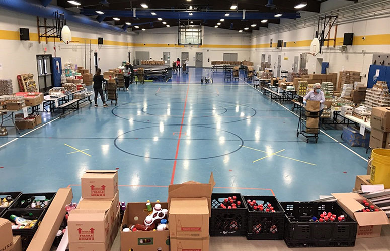 Overview of volunteer set-up for food bag packing at Ann M Jeans Elementary School